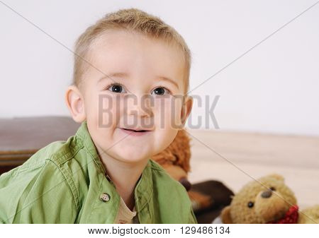 Portrait Of Little Cute Smiling Boy With His Toy On Background