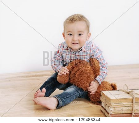 Studio Shot Of Little Cute Smiling Boy With His Toy And Books