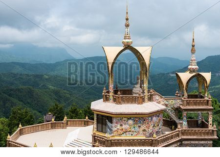 Golden sanctuary with white Buddha statue on the high mountain.