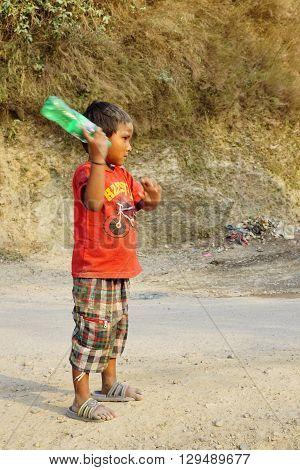 Pokhara Nepal - April 24 2016: Serious Nepali boy playing on the road