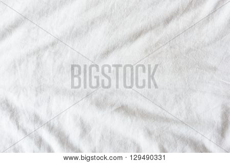 Top view of wrinkles on an untidy white bed sheet in a bedroom after a long night sleep and waking up in the morning.