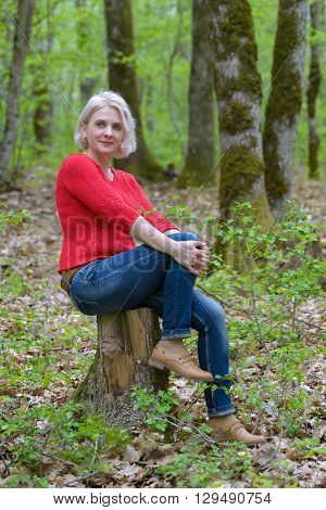 Beautiful blonde in a red sweater sits on a stump in the forest