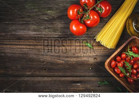 Italian food background / cooking ingredients background. Dry pasta, tomatoes, olive oil and salad leaves on wooden backdrop
