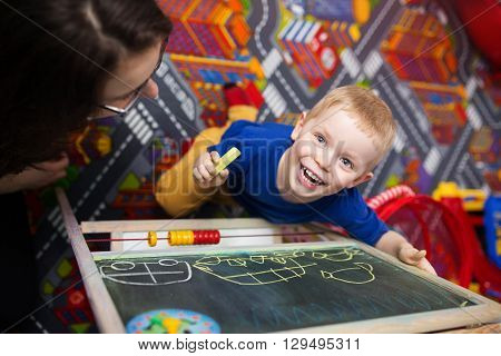 A photo of small boy drawing on the blackboard and smiling happily. His mom is looking after him.