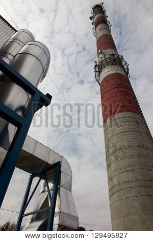 white and red high concrete chimney on sky background
