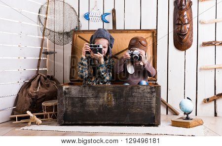 two little girls in wooden chest playing rarity cameras