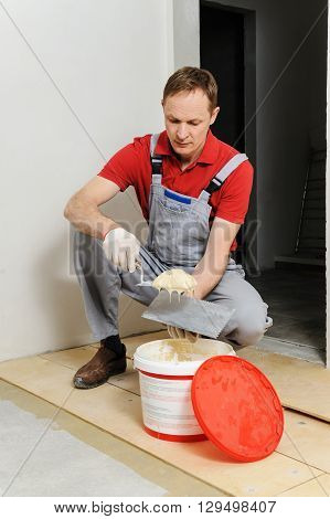Laying plywood on the floor. A worker puts glue for gluing of the plywood