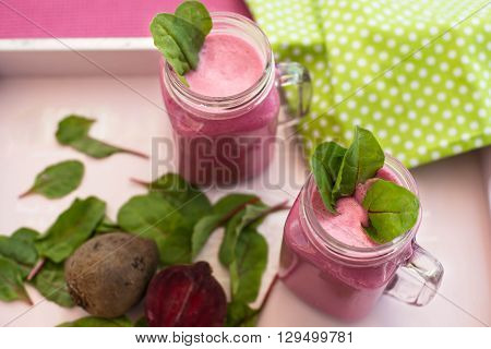 Glass of fresh beetroot juice with bets and leafs . Beetroot smoothie in jar. Pink detox. Eye bird view. Top view. poster