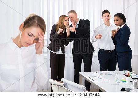 Businesspeople Gossiping Behind Stressed Female Colleague In Office poster