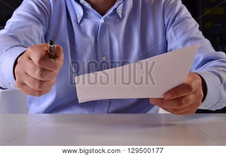 It is time to sign the document.Giving the document to sign.Business man holding a document to sign.