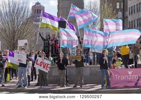 Asheville, North Carolina, USA - April 2, 2016: Crowd holds signs waves symbolic flags and protests the new North Carolina HB2 Law that restricts the rights of those who are gay or transgender on April 2 2016 in downtown Ashevile, NC