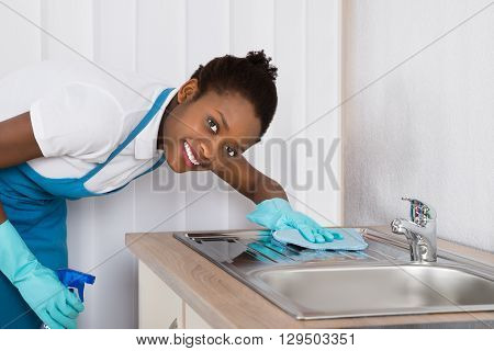 Young Happy Female Janitor Cleaning Sink With Rag And Detergent Spray Bottle poster