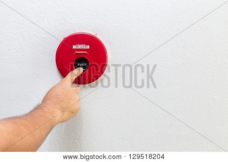 Hand With Finger Pressing Red Fire Alarm On The Wall