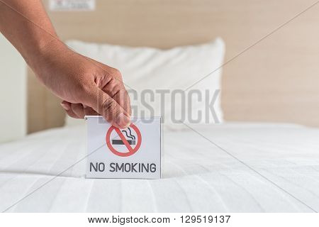 Hand Holding No Smoking Sign On The Bed In Hotel Room