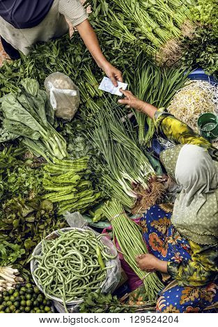 Old muslim woman selling fresh vegetables in traditional asian market. poster