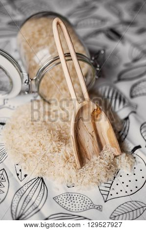 handcarved wooden scoop with long handle and white rice