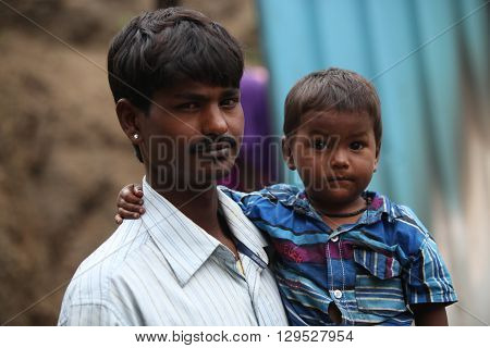 Pune India - July 16 2015: A little boy with his poor father who is a construction worker in India