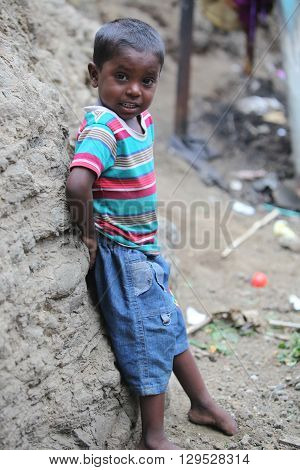 A poor Indian boy standing at a construction site where his parents work in India
