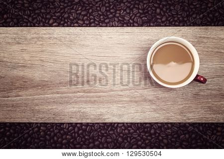 Coffee Cup And Coffee Beans On Wooden Background, Focus On Cup