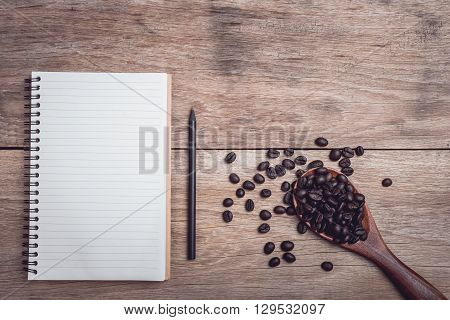 Coffee Beans And And Lined Paper On Wooden Table Top View