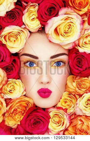 Portrait of young beautiful blue-eyed woman with fancy make-up, pout and colorful roses around her face