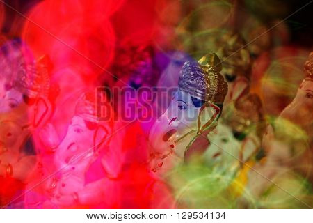 A view of traditional Ganesha idols through blur colorful lights during Ganapati festival