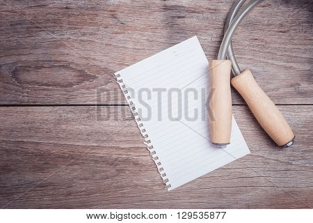 Skipping Rope And Lined Paper On Wooden Table Top View