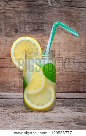 Cold lemonade with ice. Detox cocktail. Refreshing homemade lemonade on old wooden table. Detox fruit infused flavored water. Refreshing summer drink