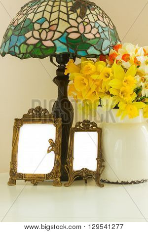 Fresh spring daffodils in white pot on table with empty art noveau  frames and vintage lamp