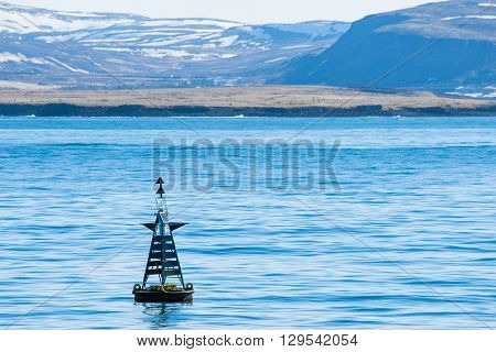 Buoy Silhouette In The Blue Ocean