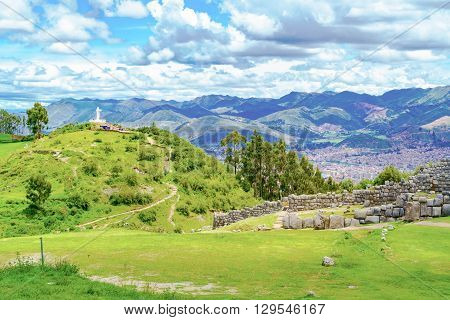 Lanscape of Saqsaywaman with the statue of Jesus Christ and aerial view of City of Cusco in Peru