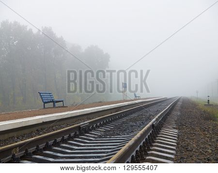 Two blue benches on the empty railroad station platform on foggy day