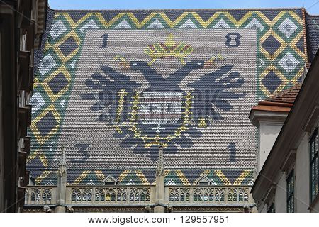 VIENNA AUSTRIA - JULY 12: Coat of Arms at St. Stephen Cathedral in Wien on JULY 12 2015. Side View of Stephansdom Basilica With Sign at Roof Tiles in Vienna Austria.