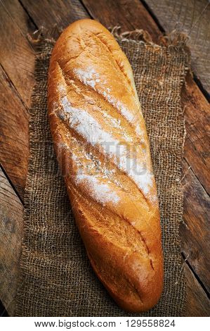 Baguette on sackcloth on planked wooden table
