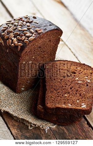 Close up photo of rustic bread sprinkled with sunflower seeds on planked wooden table