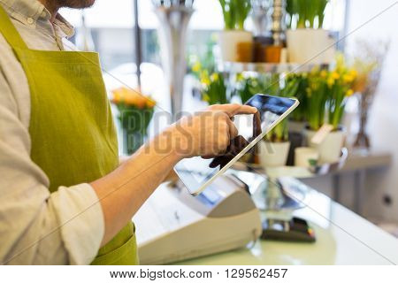 people, business, technology, sale and floristry and concept - close up of florist man with tablet pc computer at flower shop