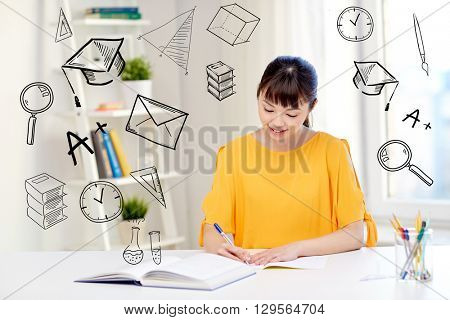 people, education, high school and learning concept - happy asian young woman student with book and notepad writing at home over doodles