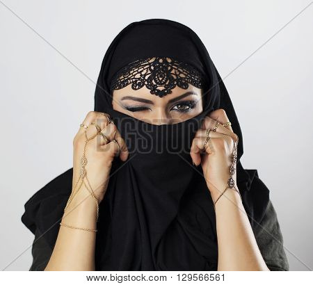 Beautiful caucasian young woman with black veil on face one eye closed fancy arabian costume