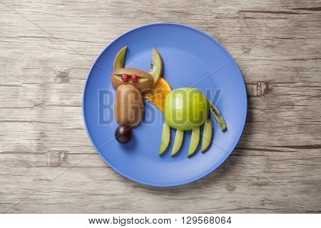 Funny wolf made of fruits on wooden desk and plate