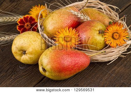 Pears decorated with dried straw and wheat on old wooden table.
