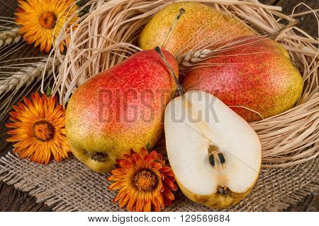 Ripe pears autumn composition on jute background