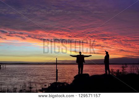 The sun sets as a storm clears, two people are at the waters edge to greet the change in weather