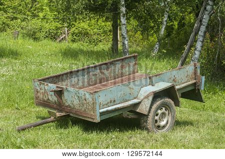 Obsolete weathered metal lightweight cargo trailer platform in farmyard