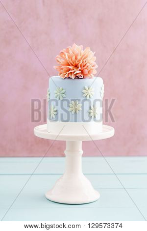 Blue fondant cake with pink sugar peony flower on cake stand