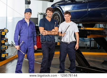 Confident Mechanics Holding Worktools At Garage