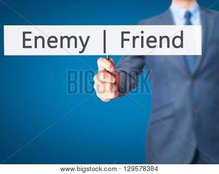 Enemy  Friend - Businessman Hand Holding Sign