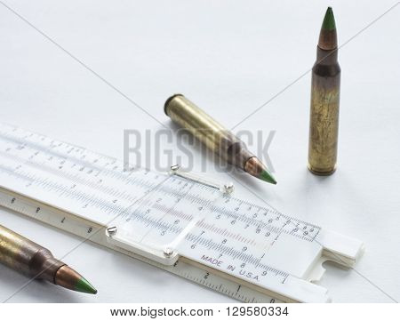 Three steel cored cartridges and a slide rule on white