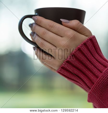 Woman in red sweater holding brown cup