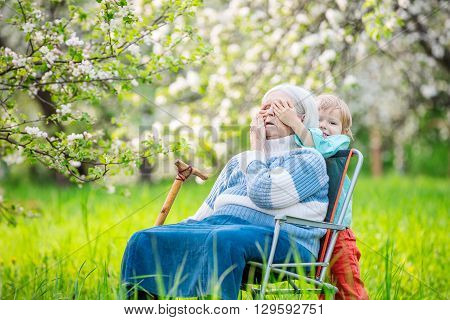 Little boy playing peekaboo with his great grandmother