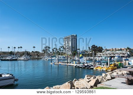 Oceanside,California,USA - July 15, 2015 : View of boats in the tourist harbor with palm and skyscraper in background